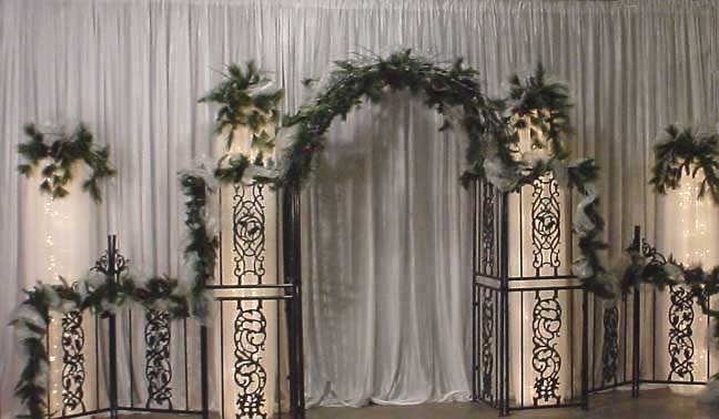 columns make a beautiful backdrop for your wedding decorated with pine
