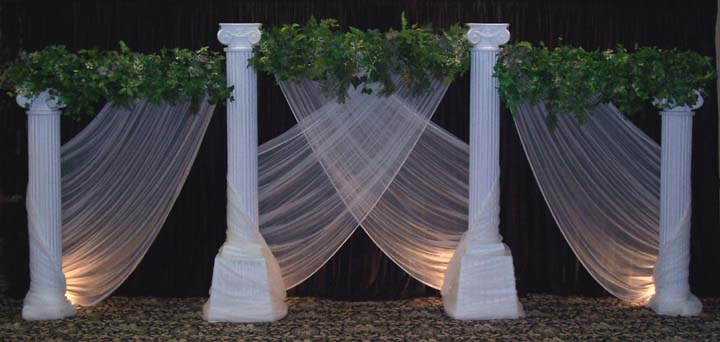 Round grecian columns with greenery bars and sweeping chiffon add a