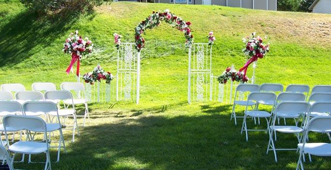 White iron backdrop is set up outside for a simply elegant garden wedding.